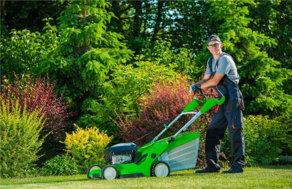 photo of man mowing the yard with a lawn mower